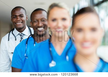 portrait of african male doctor standing in a row with medical team