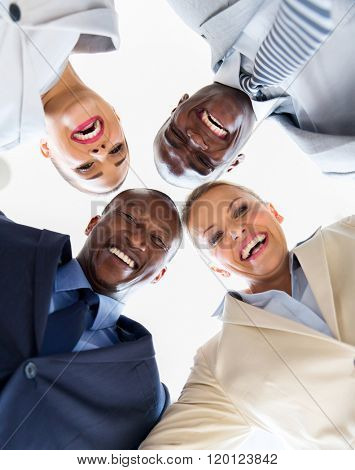 group of cheerful business people in a circle looking down