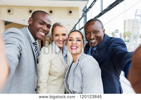 successful multiracial business team taking selfie together