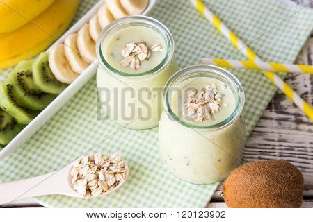 Banana Smoothie With Kiwi And Oats On A Light Wooden Table. Protein Diet. Healthy Food Concept.