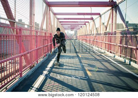 Young skateboarder speed through the pedestrian walkway on Williamsburg Bridge NYC. Photographed in Feb 2016.