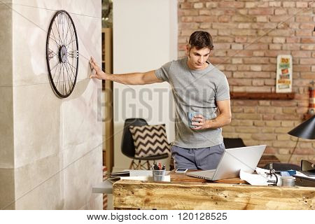 Casual man using laptop, drinking tea at home, standing by desk.
