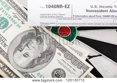 Close Up View Of Red Arrow And One Hundred Dollar Bill And Us Tax Form On Dart Board.