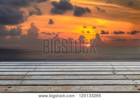 Wooden platform beside tropical sea with sunset