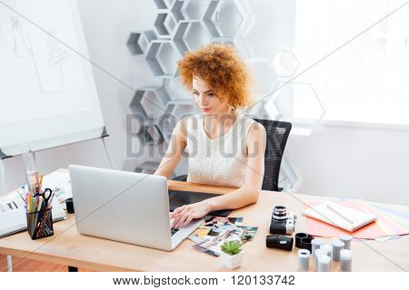 Beautiful curly young woman photographer sitting on workplace and using laptop with graphic tablet