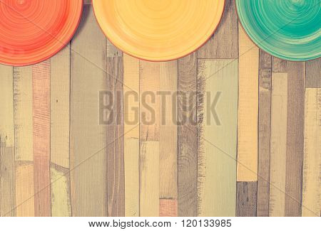 ?olored Plates On Wooden Background.