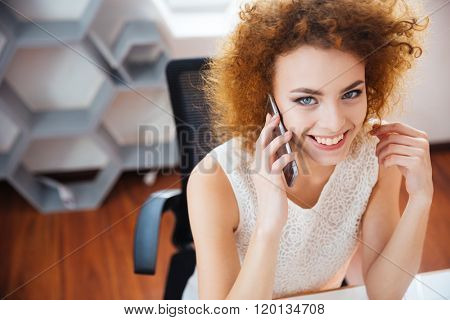 Smiling beautiful business woman with curly red hair talking on mobile phone on workplace in the office