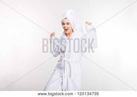 Happy excited young woman in bathrobe with towel on her head dancing over white background