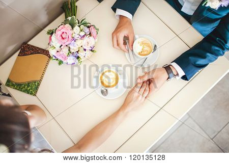 Wedding couple at cafe, top view. Man holds woman's hand, drinks espresso. Bride and groom coffee br