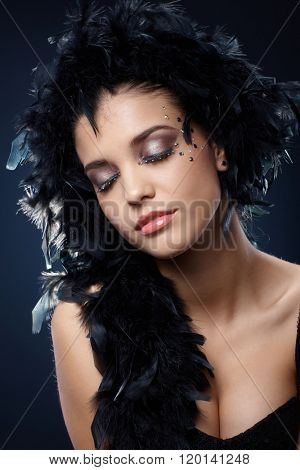 Elegant and beautiful girl with sparkly makeup and black boa posing with eyes closed.