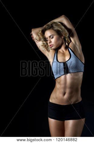 Sport  fitness girl with slim muscular body posing in studio