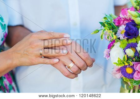 hands of bride and groom with rings and wedding bouquet