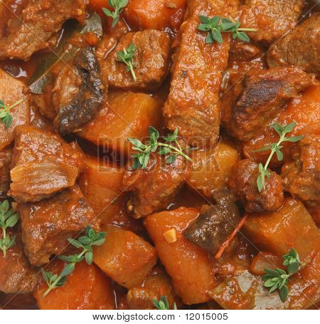 Beef stew with carrots, swede, tomato, mushroom and shallots. Garnished with sprigs of thyme.
