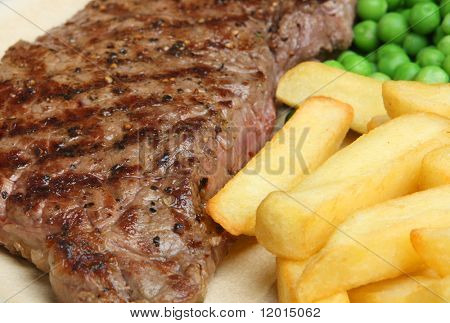Char-grilled sirloin steak with chips and peas.