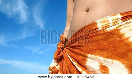 A young woman wearing a sarong against a blue sky.