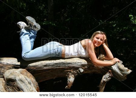 A young woman laying on a tree stump.