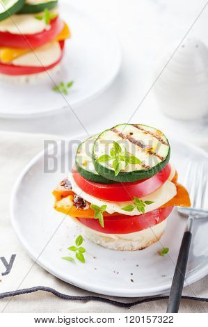 Grilled vegetables and cheese gratin stacked on a plate with fresh basil on white background