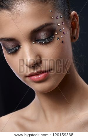 Closeup facial portrait of attractive young woman wearing elegant glittering makeup with strasses, eyes closed.