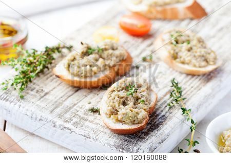 Bruschetta with green olives paste, tapenade on a white wooden background