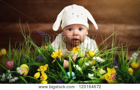 Happy Child Baby Dressed As The Easter Bunny Rabbit On The Grass With Flowers
