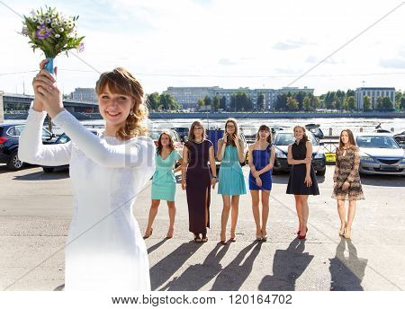 Bride Is Ready To Throw Away Her Wedding Bouquet. Focus On Bridesmaids.