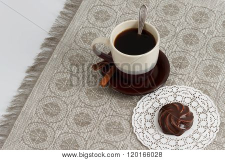 Cup Of Coffee With Cinnamon And Chocolate Marsh-mallow On Mat Against Monochromic Tablecloth With Co