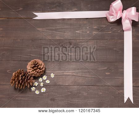 The Arrangement Of Pine Cones And Ribbon Are On The Wooden Background. Space For Your Text And Your