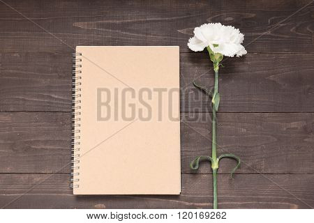 Notebook And Carnation Flower Are On The Wooden Background