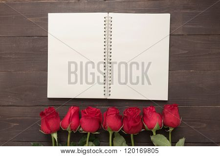 The Arrangement Of Red Roses Flower With Notebook Are On The Wooden Background