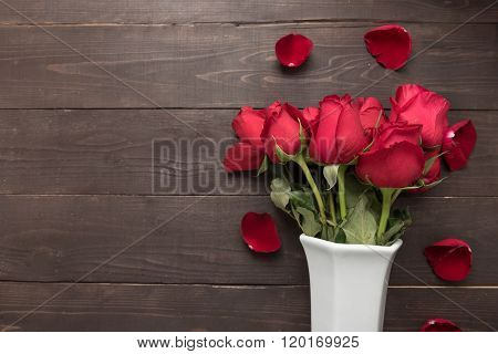 Red Roses Flower Are In The White Vase On The Wooden Background