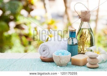 Spa and wellness massage setting Still life with essential oil, salt and stones Outdoor background C