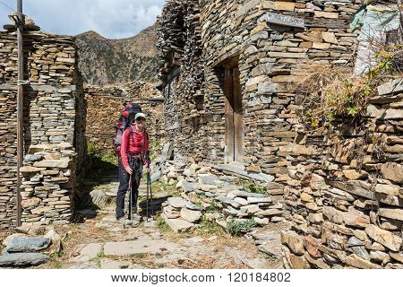 Female trekker passing traditional village.