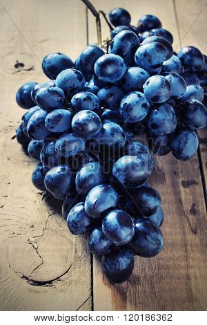 Cluster of Blue Grapes on Old Wooden Background.