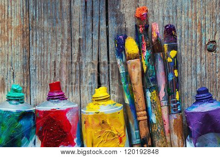 Tubes Of Oil Paint And Artist Paint Brushes Closeup On Wooden Background.