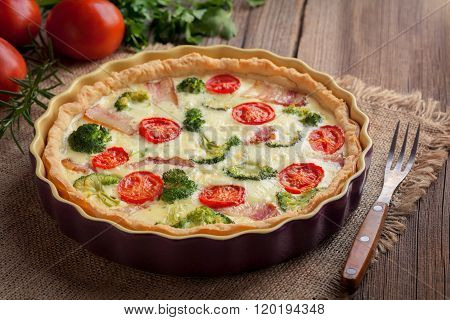 Traditional homemade quiche lorraine tart pie with broccoli, bacon