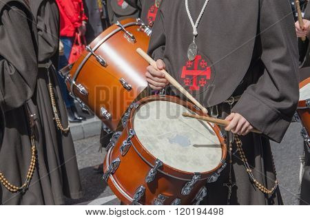 Members of a brotherhood marching and playing drums in a Holy week procession