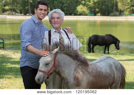 Grandfather And Grandchild Stroking Pony