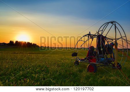 Paraglider on sunset, sunlight between trees, paraglider with motor after landing