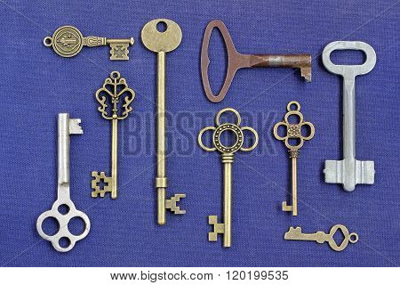 Metal Keys From Different Locks On A Blue Background.