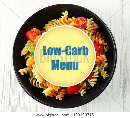 Delicious macaroni dish ant text Low-Carb Menu on grey wooden background