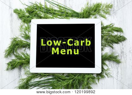Low-Carb Menu on tablet pc screen with fresh herbs on wooden background