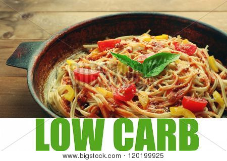 Spaghetti Bolognese in pan and text Low Carb on wooden background