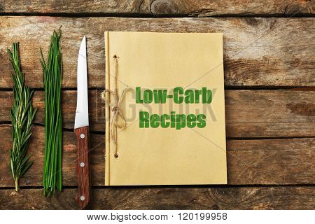Text Low-Carb Recipes in recipe book on wooden background