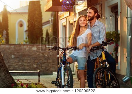 Close up of young loving couple with bikes nearby wall