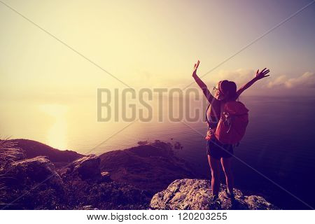 cheering young woman hiker open arms on sunrise seaside mountain top