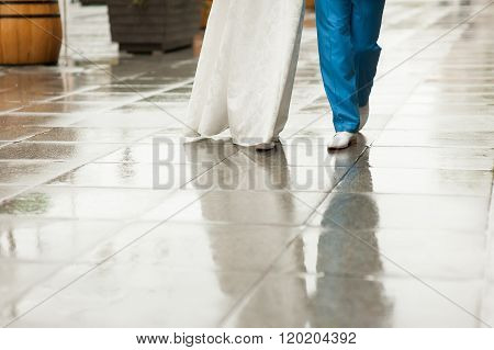 Bride And Groom Walk Along Wet Pavement Street