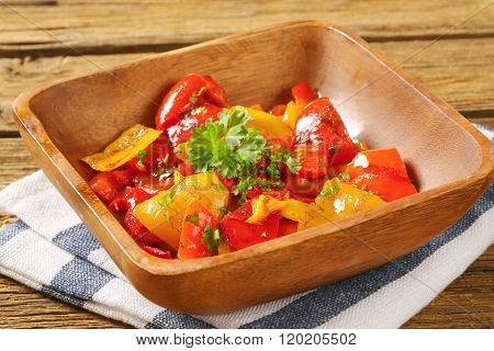 bowl of grilled peppers on striped dishtowel - close up