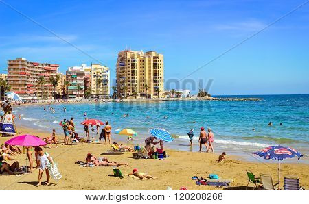 Sunny Mediterranean Beach, Tourists Relax On Sand, People Bathe In Sea, Torrevieja, Spain