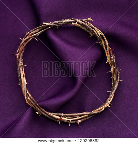 high-angle shot of a recreation of the crown of thorns of Jesus Christ on a purple drapery