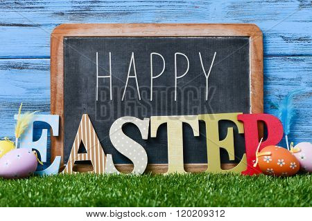some decorated eggs on the grass, and the text happy written in a chalkboard and three dimensional letters forming the word easter, against a blue rustic wooden background